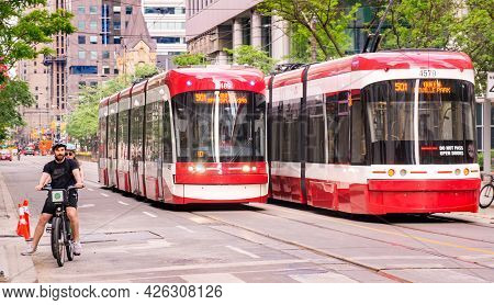 Toronto, Canada - 06 05 2021: New Bombardier-made Ttc Streetcars Sharing The Road With Cyclists On K