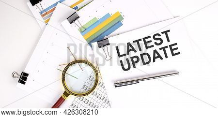 Latest Update Text On White Paper On The Light Background With Charts Paper