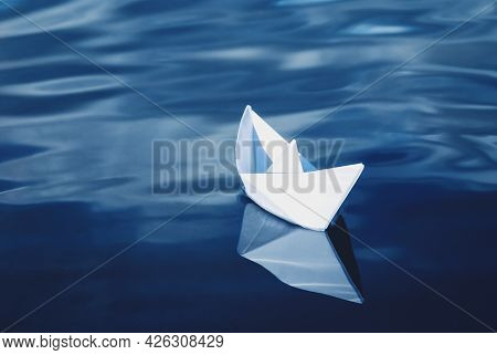 White Paper Boat Floating In Blue Sea