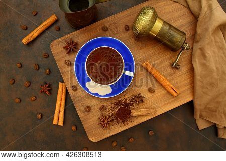 Coffee Beans And Ground Coffee In Wooden Spoons On Brown Background. With Coffee Pot, Blue Coffee Cu