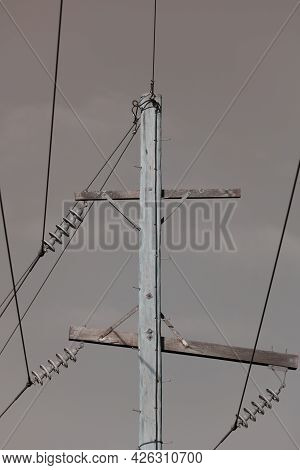 Photograph Of A Wooden Telephone Post And Cables Against A Blue Sky