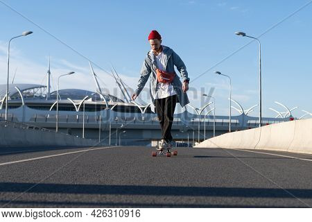 Street Fashion And Urban Lifestyle: Hipster Man Dressed In Trendy Casual Clothes Longboarding On Cit