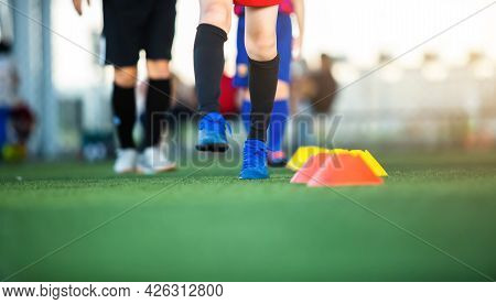 Selective Focus To Cone Marker With Blurry Soccer Team Is On Green Artificial Turf.