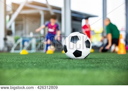 Selective Focus To Soccer Ball On Green Artificial Turf With Blurry Soccer Team Is Training.