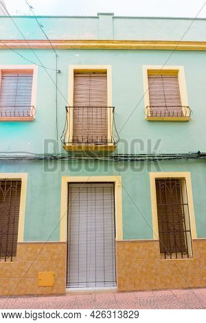 Orba, Village Streets And Buildings, Building Facade In Green And Brown. Spain