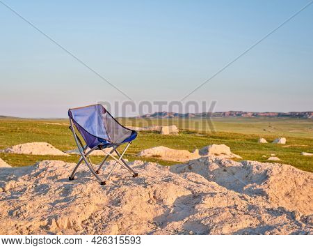 empty folding chair in the middle of nowhere, early morning in the badlands of Pawnee National Grassland in Colorado