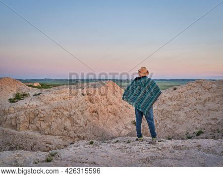 Man in a Mexican poncho and cowboy hat is waiting at dawn for summer sunrise at prairie - Pawnee National Grassland in Colorado