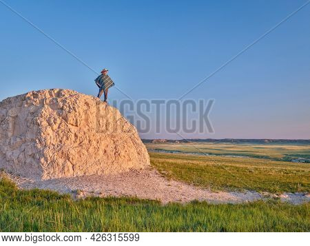 Man in a Mexican poncho and cowboy hat is enjoying summer sunrise at prairie - Pawnee National Grassland in Colorado