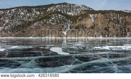 On The Frozen Lake There Are Patterns Of Intersecting Cracks And Snow. On The Shore There Are Wooded