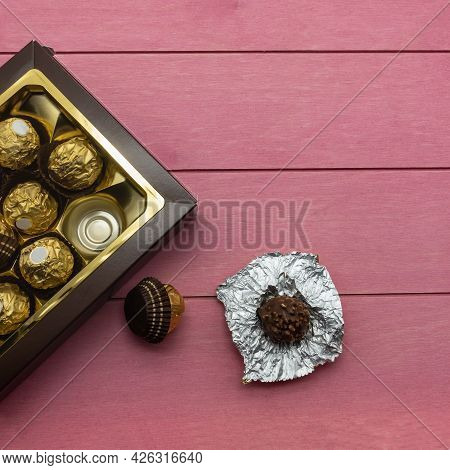 Chocolate Candies, Wrapped In Golden Foil, Packed In A Brown Cardboard Box. Nearby, On Pink Boards,