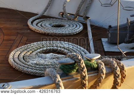 Mooring rope and coils of nautical cord on wooden deck of moored ship. Selective focus.