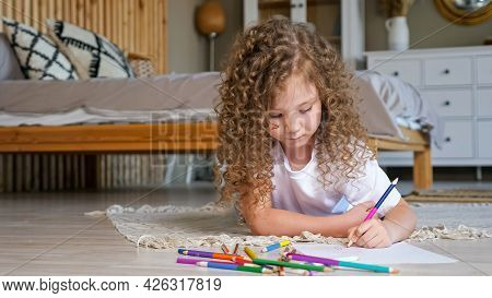 Little Preschooler Girl With Long Loose Curly Hair Takes Coloured Pencil And Draws Lying On Wooden F