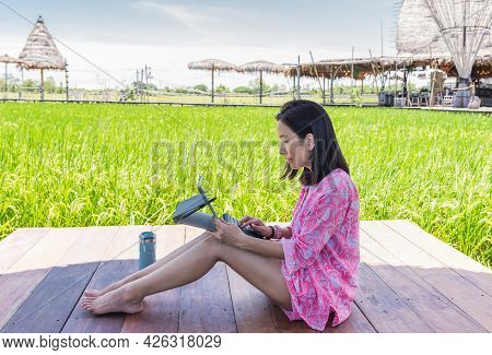 Beautiful Woman Working On Laptop Sitting On Wooden Deck Outdoor