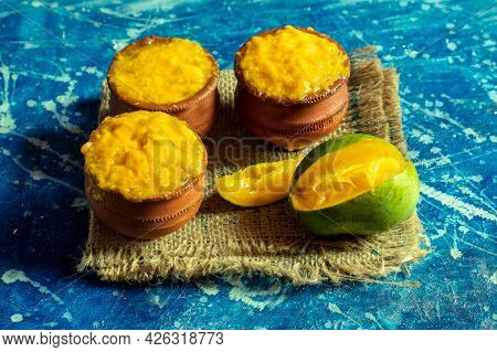 Aam Ras Or Ripe Mango Pulp In Earthen Bowls On Burlap Fabric Isolated On Bluish Background