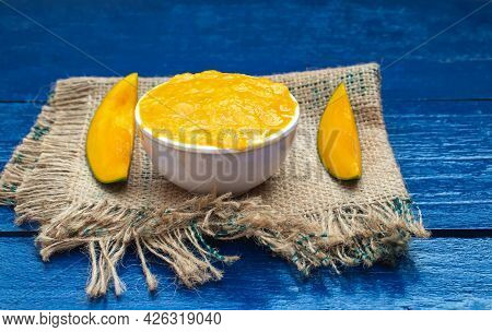 Ripe Mango Pulp Or Aam Ras And Cuts On Burlap Fabric Isolated On Wooden Background In Horizontal Ori