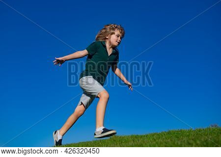 Child Boy Running On Grass Field And Dreaming. Kids Play On Summer Field. Active Kids Healthy Outdoo