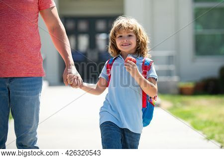 American Father And Son Walking Trough School Park. First Day At School. Father Leads A Little Child