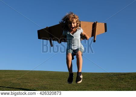 Funny Child Jumping And Running With Toy Jetpack. Child Pilot Astronaut Or Spaceman Dreams Of Flight