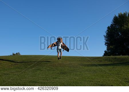 Child Running Jumping And Flying With Toy Plane Wings On Grass In Park. Child Imagination Dream To B