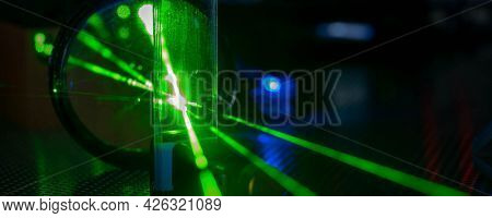 Green laser on optical table in a quantum optics laboratory