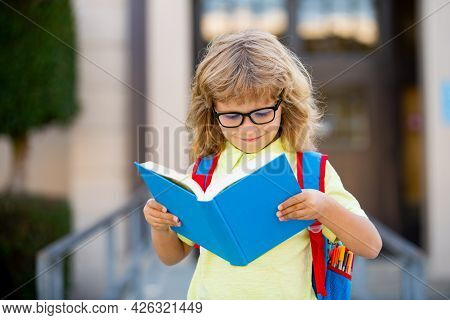 Happy Smiling Kid In Glasses Is Going To School For The First Time. Pupil Go Study. Child Boy With B