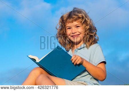 Cute Lovely Child Reading Book On Blue Sky Background Outside. Kid Read Book In Park.