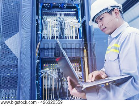 A Man With A Laptop Sits In The Server Room Of The Data Center. The System Administrator Works Near