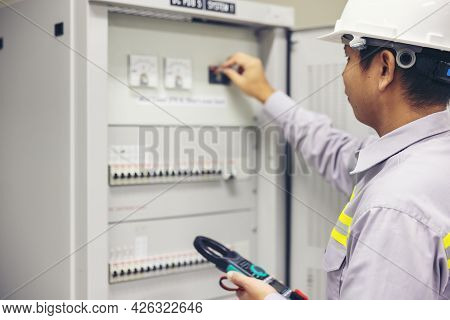A Male Electrician Works In A Switchboard Electrical Terminal Junction Box. Control Panel With Multi