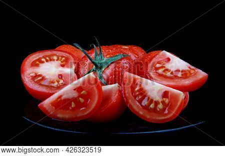 Sliced Red Tomatoes On A Black Plate Are Isolated On A Black Background. Clipping Path.
