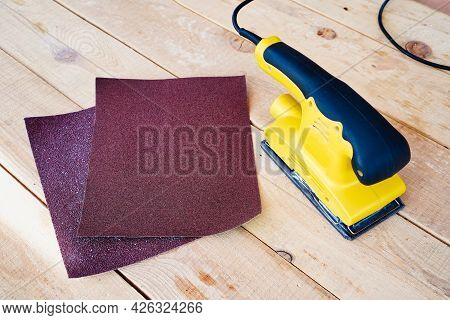 Manual Electric Yellow Grinder. Two Pieces Of Sandpaper, Abrasive. Wooden Surface For Processing.