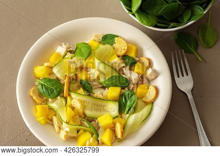 Plate With Salad And Fork Close-up On A Brown Background, Salad Of Cucumber And Chicken Breast, Mozz