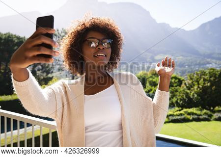 Happy african american woman on sunny balcony of country home making video call on smartphone. spending free time at home.