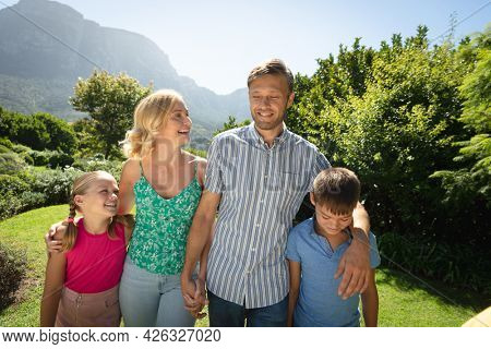 Happy caucasian couple with daughter and son outdoors, walking in sunny garden. family quality time, leisure time concept. family enjoying quality free time together.