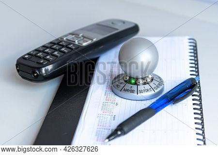 Table With Organizer, Pen, Phone And Wheel Of Opportunity, Pointer On Maybe, Accidental Luck Concept