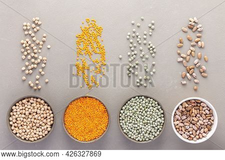 Different Types Of Legumes In Bowls And Scattered In The Background, Green Peas And Pinto Beans, Chi