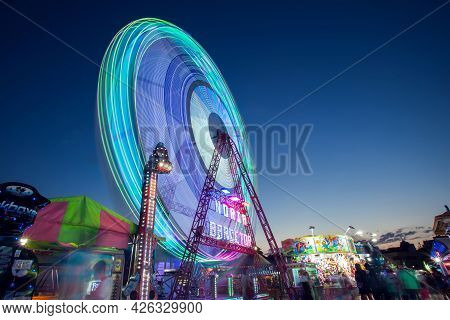 Spain, Torrevieja, 27.06.2021. A Carousel With Bright Lights Of Different Colors Long Exposure