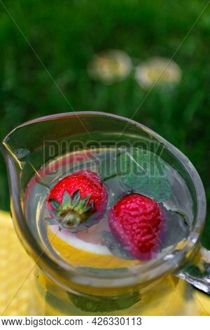 Defocus Two Strawberry, Slice Lemon And Leaves Of Mint In Glass Jug Of Lemonade On Yellow Board. Blu