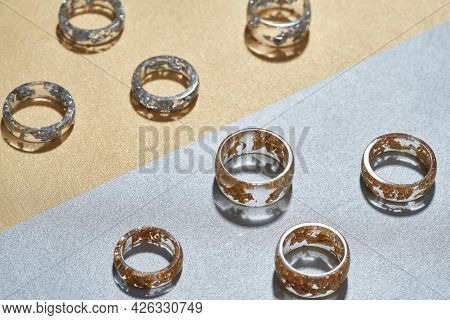Assortment Of Clear Resin Rings With Golden And Silver Filling Lying On Gray Orange Background. Jewe