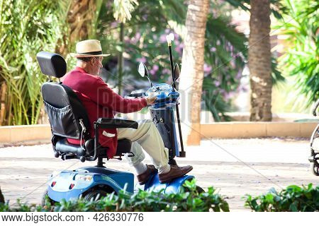 Torrevieja, Spain, 24.05.2021, Senior Man Using Electric Wheelchair In The Park. Lifestyle And Indep
