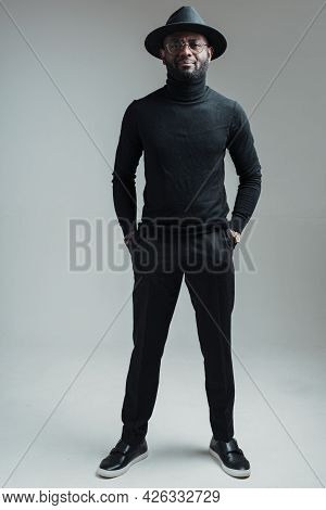 Full-length Photo. Handsome African American Man In Glasses In A Hat And Black Clothes Stands With H