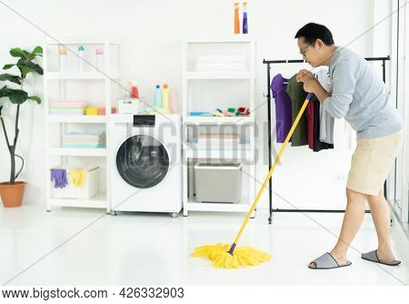Asian Man Wearing Grey Sweater Washing Floor With Mopping Stick And Bucket In Laundry Room Of Bright