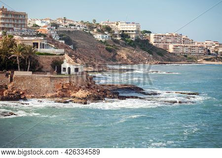 Torrevieja, Spain, 21.05.2021, Landscape Of Rocky Beach And Waves At Mediterranean Sea In Torrevieja