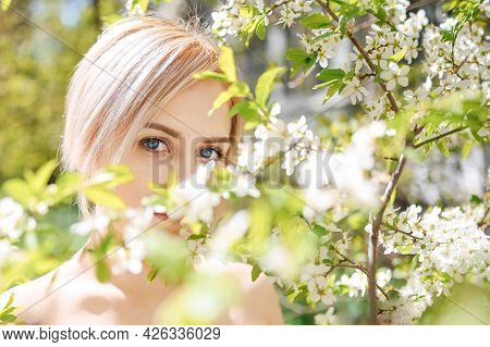 Close Up Young Beautiful Blonde Woman With Blue Eyes Posing In Blooming Spring Garden With White Flo