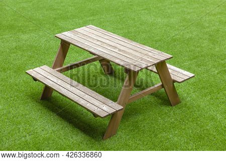 The Chair Is Made Of Wood, Set On Synthetic Grass.