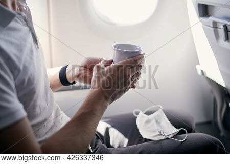 Passenger With Face Mask Drinking Coffee In Airplane. Themes Traveling During Pandemic Covid-19.