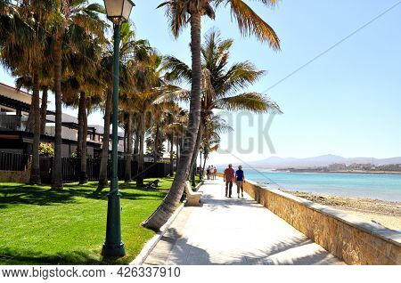 View Of The Promenade With Beautiful Palm Trees Around It, The Beach And The Blue Ocean Water In Cas