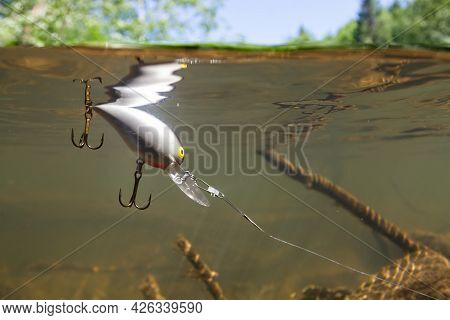 Fishing With Spinning. On The Surface Of The Greenish River Water, Covered With Ripples, A Light Gra