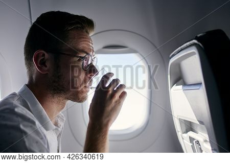 Portrait Of Passenger During Flight. Young Man Drinking Water From Plastic Cup.
