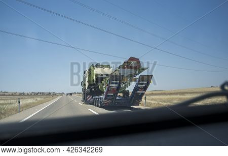 Driving Behind Heavy-duty Truck Carrying Harvester. Heavy Duty Transports. View From The Inside Of T