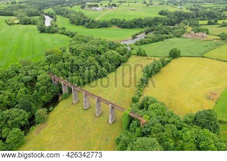 Aerial View Of An Old Bridge With Bridgetown Abbey In The Background, A 13th-century Augustinian Mon